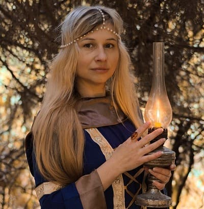 Heathen woman in the woods holding a candle lamp
